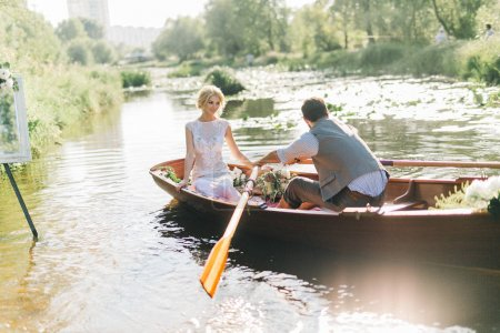 young wedding couple in boat. man rowing