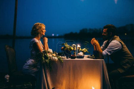Photo for Happy young couple of newlyweds having dinner   on pier - Royalty Free Image