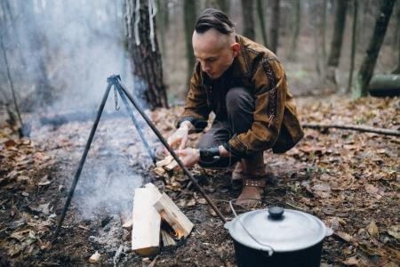 The guy fueling the fire for dinner in the woods