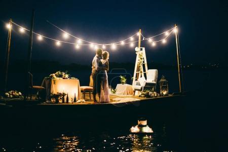 Photo pour Heureux jeune couple de jeunes mariés sur jetée - image libre de droit