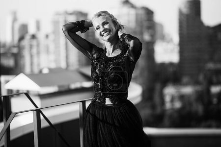 Attractive blonde in black dress posing on roof, black and white