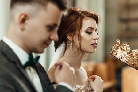 Handsome groom and beautiful bride in church with priest at wedding ceremony