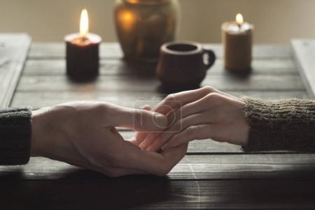 Photo pour Soirée romantique par des amoureux des bougies. Les mains d'un homme et d'une femme s'étreignent . - image libre de droit