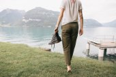 cropped shot of girl holding shoes and walking barefoot on grass near beautiful mountain lake