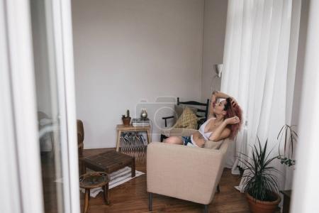 Photo pour Belle fille en soutien-gorge et denim Short reposant sur le fauteuil dans appartement confortable - image libre de droit