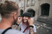 selective focus of man putting hat on beautiful smiling young woman while walking together on street in Bern, Switzerland