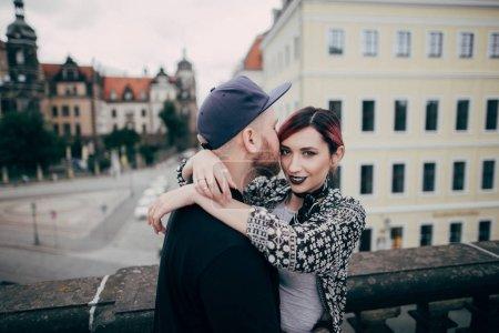 Foto de Hombre guapo besos a hermosa mujer joven mirando a cámara mientras pie juntos sobre puente en Dresde, Alemania - Imagen libre de derechos