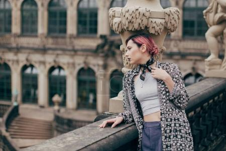 beautiful pensive young woman looking away while standing near baroque palace in Dresden, Germany