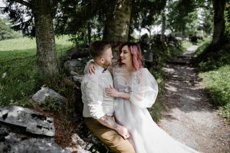 happy young bride and groom hugging and smiling each other in beautiful mountain valley, Alps