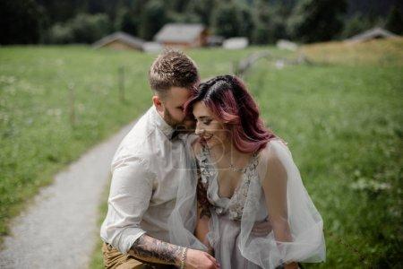 Photo pour Belle jeune mariée et marié embrasser et rire dans la vallée de la montagne, Alpes - image libre de droit
