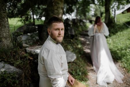 Photo pour Beau jeune marié regardant caméra et mariée marchant sur le sentier de montagne dans les Alpes - image libre de droit