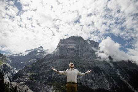 Photo for Low angle view of handsome young man standing with open arms in beautiful mountains, Alps - Royalty Free Image
