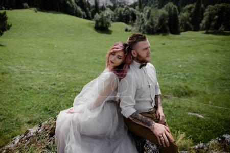 Photo pour Belle jeune mariée et marié assis dos à dos sur la prairie de montagne verte dans les Alpes - image libre de droit