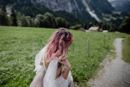 Photo pour Belle jeune mariée marchant dans la vallée de montagne dans les Alpes - image libre de droit