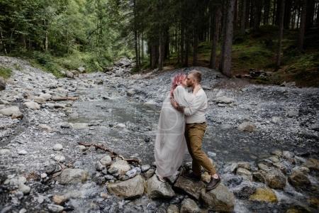 Photo pour Beau jeune couple de mariage baisers tandis que debout sur les rochers dans la rivière de montagne rapide, Alpes - image libre de droit