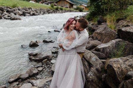 Photo pour Beau couple de mariage heureux embrassant et embrassant près de la rivière de montagne dans les Alpes - image libre de droit