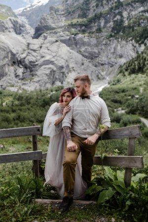Photo pour Beau jeune couple de mariage debout près d'une clôture en bois dans les Alpes - image libre de droit