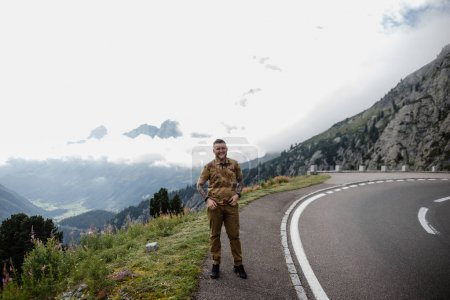handsome young man standing on asphalt road in mountains and smiling at camera, Alps