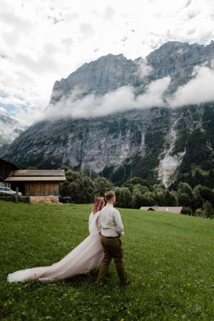 Photo pour Jeune marié marchant sur une prairie verdoyante avec des nuages dans les Alpes - image libre de droit