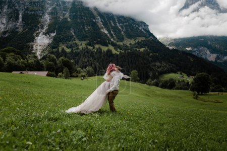 Photo for Young bride and groom embracing on green mountain meadow in Alps - Royalty Free Image