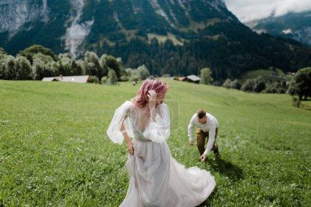 Photo pour Mariée heureuse en robe de mariée et marié marchant sur la prairie de montagne verte dans les Alpes - image libre de droit