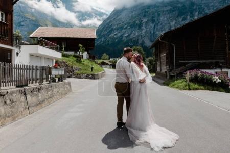 Photo pour Vue arrière de couple embrassant et embrassant sur la route en ville dans les Alpes - image libre de droit