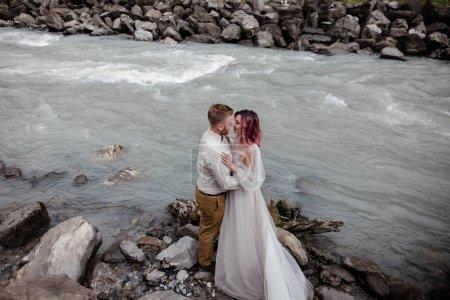 Photo pour Jeune mariée et marié câlins tout en se tenant sur la rive de la rivière de montagne dans les Alpes - image libre de droit
