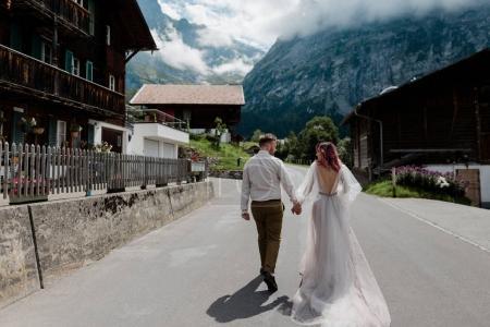 Photo pour Vue arrière du couple tenant la main et marchant sur la route en ville dans les Alpes - image libre de droit