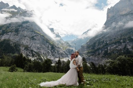 happy bride in wedding dress and groom on green mountain meadow with clouds in Alps