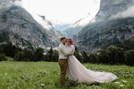 happy bride and groom hugging on green mountain meadow with clouds in Alps