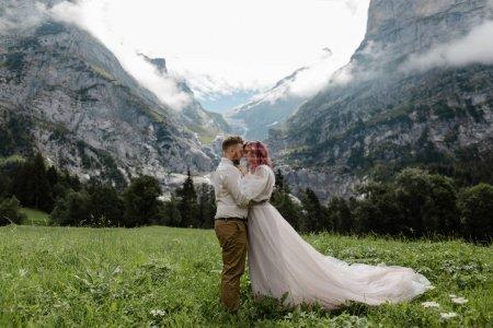 Photo pour Heureux marié et mariée étreignant sur la prairie de montagne verte avec des nuages dans les Alpes - image libre de droit