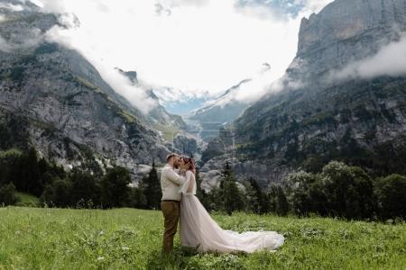 Photo pour Heureux mariés embrassant et embrassant sur la prairie verdoyante de montagne avec des nuages dans les Alpes - image libre de droit