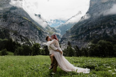 happy bride in wedding dress and groom embracing on majestic meadow with mountains and clouds in Alps