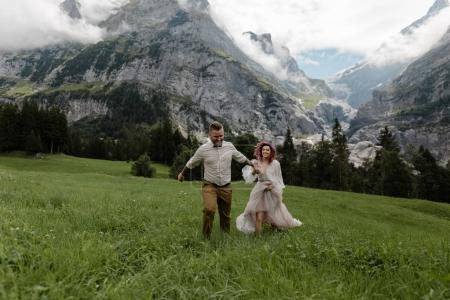 happy bride in wedding dress and groom holding hands and walking on alpine meadow