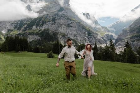 happy bride and groom holding hands and walking on alpine meadow with clouds