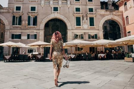 Photo for Back view of elegant glamorous barefoot girl in golden dress walking in Verona, Italy - Royalty Free Image