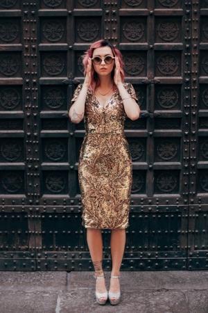 Photo pour Élégante fille aux cheveux roses en robe glamour et lunettes de soleil posant à la porte dans la vieille ville - image libre de droit