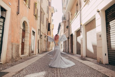 Photo for Back view of elegant girl in glamorous dress on street of Verona - Royalty Free Image