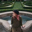 Stylish girl with pink hair sitting at fountain in...