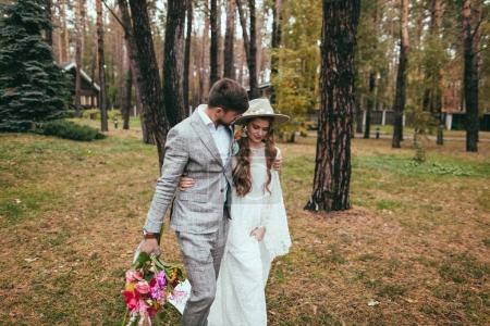 beautiful bride in wedding dress and groom hugging and walking in forest