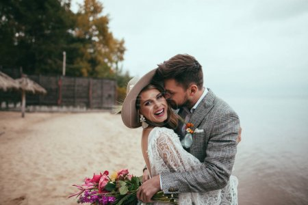 Photo for Happy bride and groom in boho style embracing on beach - Royalty Free Image