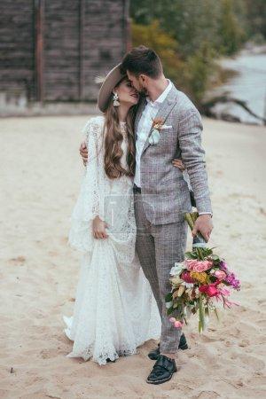 Photo pour Belle mariée et marié dans le style boho baisers sur la plage - image libre de droit