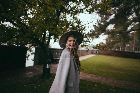 attractive smiling girl in stylish jacket and hat
