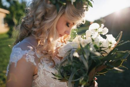 Photo for Side view of beautiful young blonde bride holding wedding bouquet - Royalty Free Image