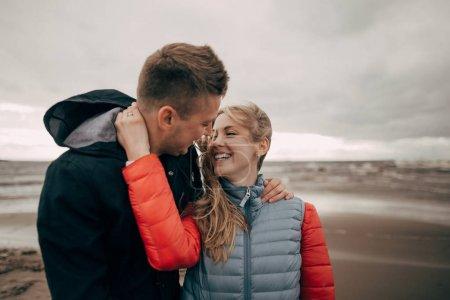 Photo pour Beau jeune couple heureux embrassant sur le bord de la mer - image libre de droit