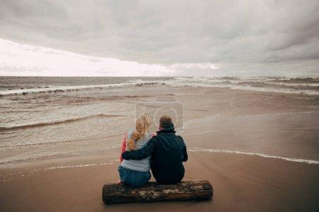 Photo pour Vue arrière du jeune couple assis sur le rondin et regardant la belle mer Baltique ondulée - image libre de droit