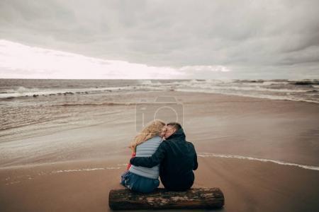 Photo pour Vue arrière du jeune couple assis sur Journal et baiser près de la mer Baltique - image libre de droit