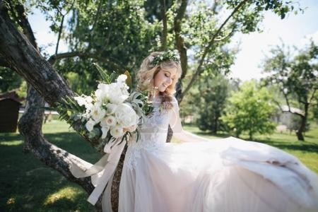 Photo for Beautiful young bride in white dress and floral wreath holding wedding bouquet outdoors - Royalty Free Image