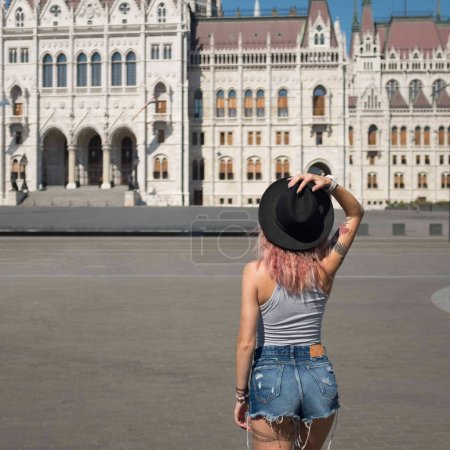 Photo for Back view of young woman in hat looking at parliament building in budapest - Royalty Free Image
