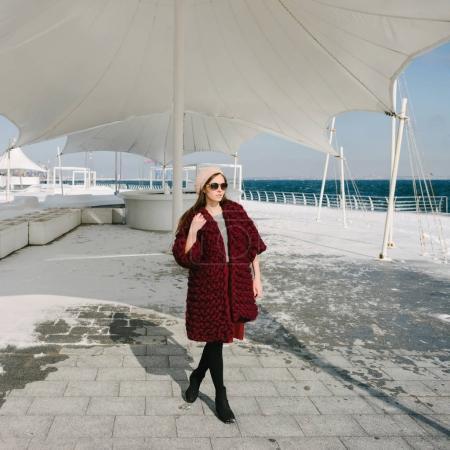 beautiful girl in sunglasses and burgundy merino wool cardigan walking on quay